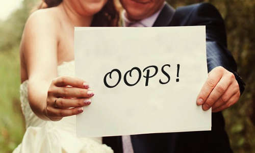 Casal segurando  um cartão escrito OOPS!