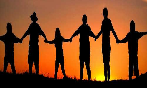 Família de mãos dadas sob o por do sol